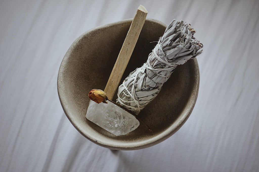 smudging sage wood and clear crystal rock placed in a bowl