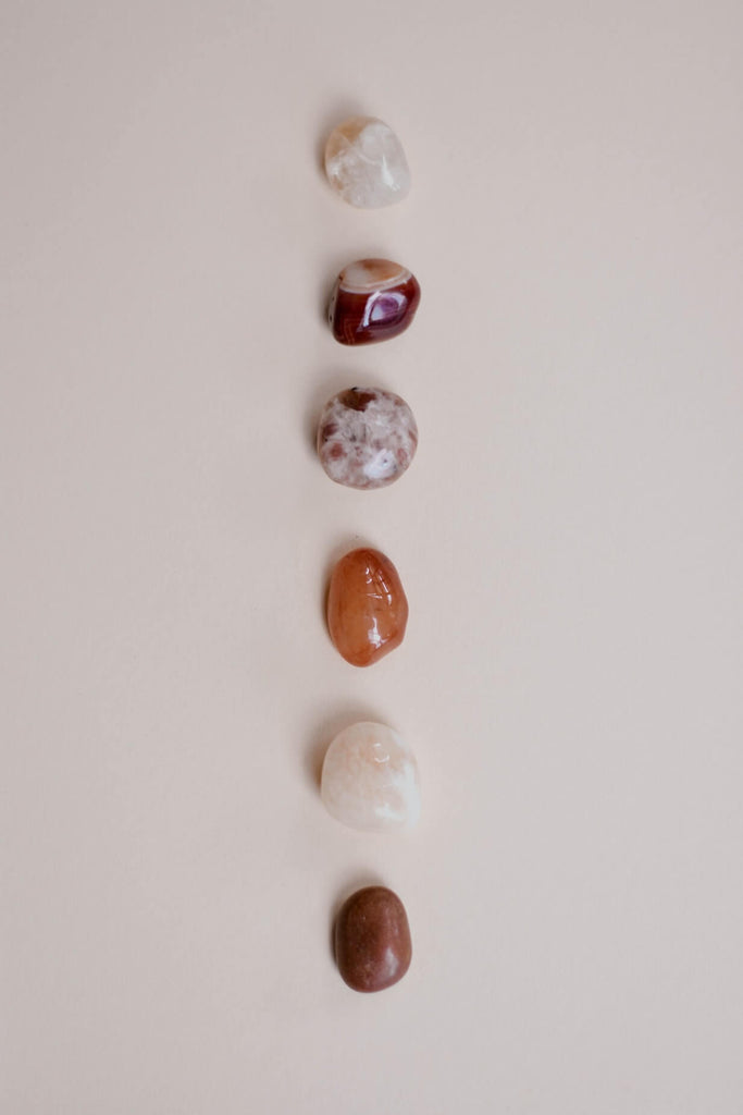 six different types colors of smooth stones arranged vertically
