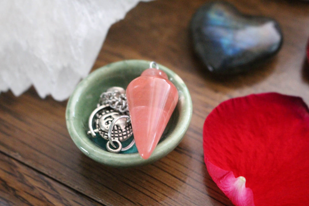 pink triangular smooth crystal necklace pendant silver charms placed on a tiny green bowl