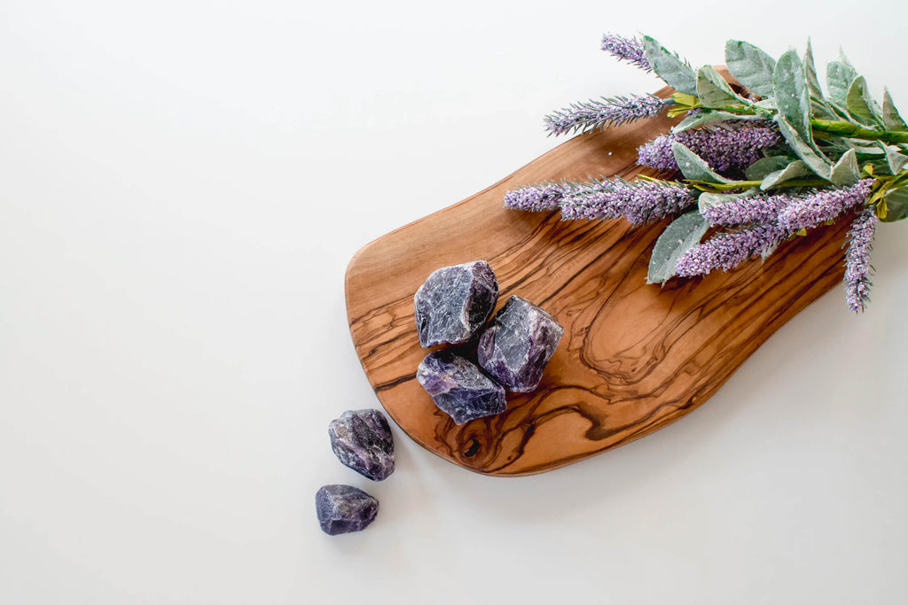 raw unpolished purple rocks placed on a wooden surface beside lavender flowers