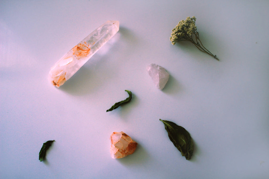 pieces of crystal rocks arranged on a white surface with flowers and leaves