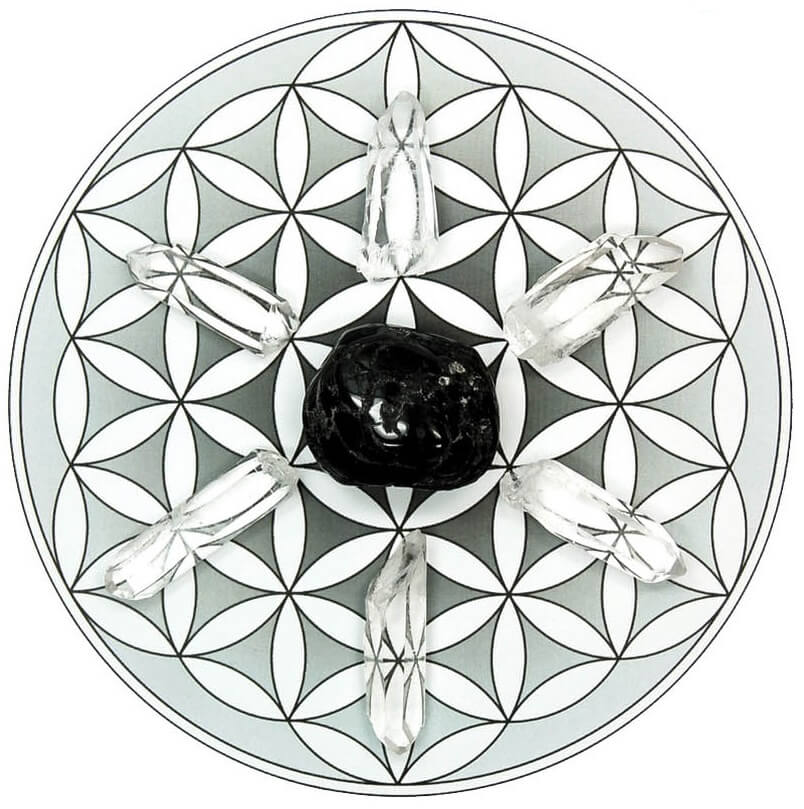 crystal rocks arranged in a circle black crystal in the middle placed on a crystal grid