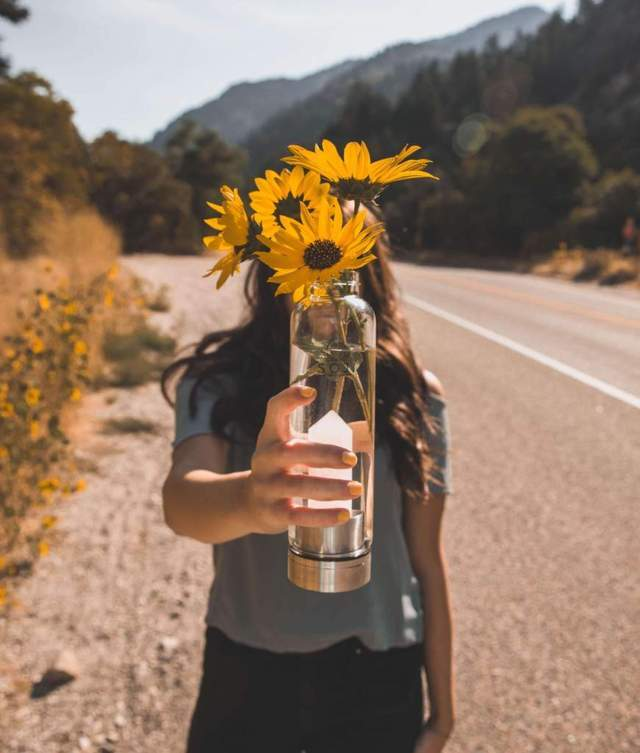woman standing by a roadside carrying a clear white crystal bottle with flowers inside