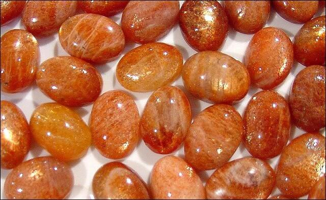 many pieces of smooth polished orange stones top close up view