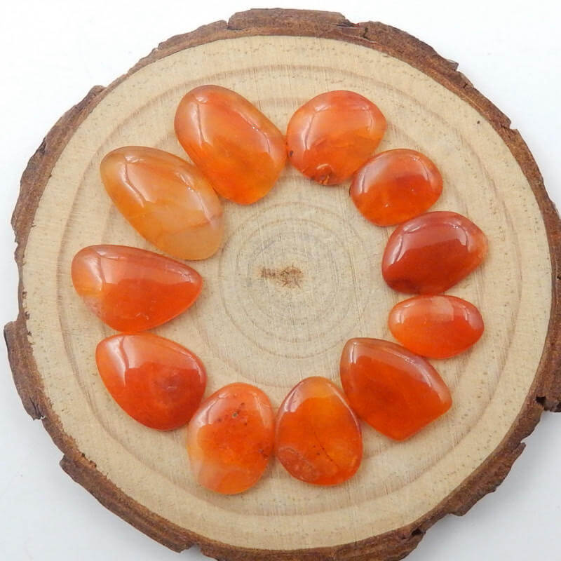 pieces of smooth orange stones arranged in a circle placed on a wooden surface