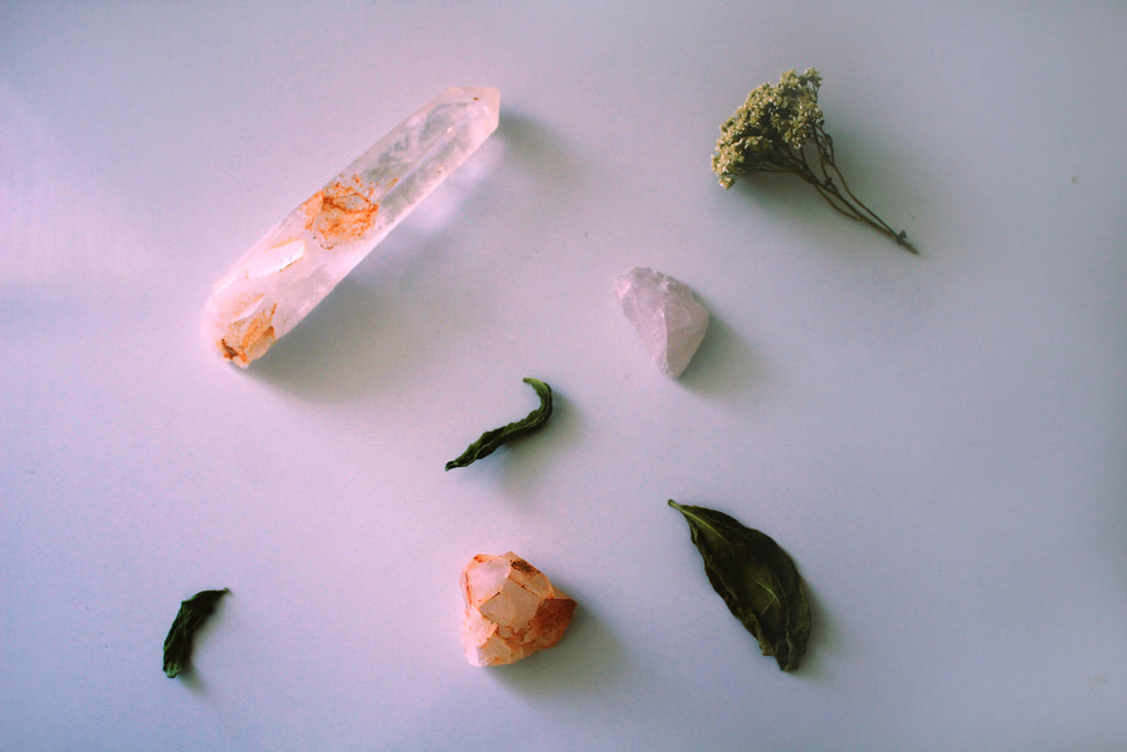 three pieces of crystal rocks dried flowers white background