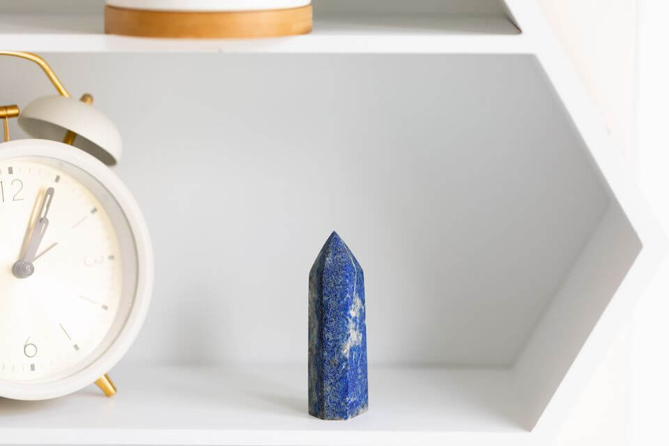 one piece of smooth polished blue crystal prism shaped placed on a white shelf