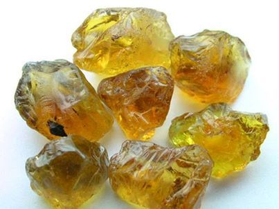 pieces of unpolished yellow crystal rocks close up view white background