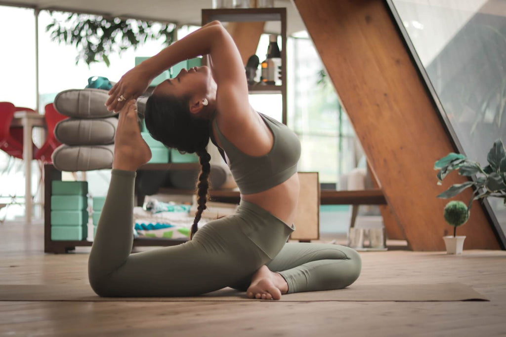woman wearing dark green outfit doing yoga pose