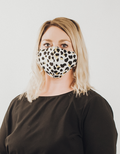 Woman with short blonde hair wearing a black, gold and white leopard spot face mask looking at camera