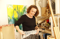 Abstract expressionist artist Anja Stemmer in her art studio with modern abstract acrylic artwork in the background. The contemporary abstract artist with painting acrylic on canvas and art store