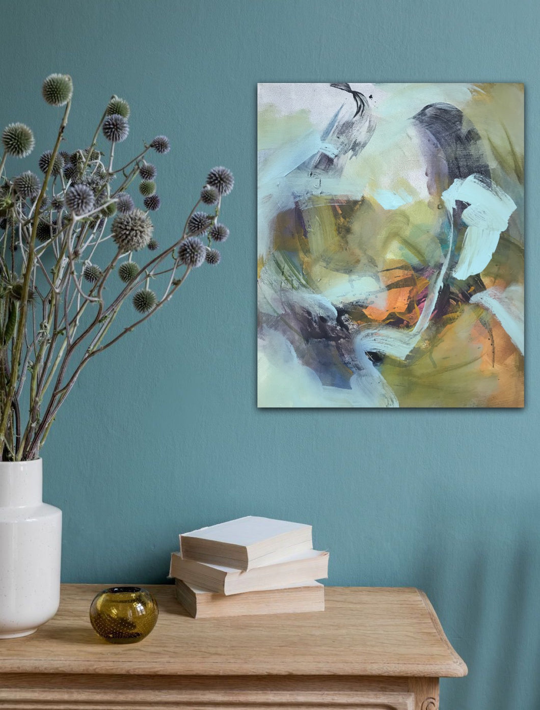 Abstract expressionist art on a turquoise colored wall over a table with books and plants- modern artwork and abstract portrait