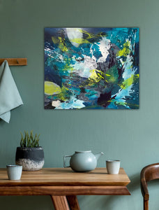 "Abstract expressionist artwork ""Aquamarine"" with blue, green and white shapes, on a colored wall and a dining table with tea pot - modern artwork. A modern acrylic painting by abstract artist Anja Stemmer. Visit my Picture Shop for affordable art online: Buy abstract paintings, modern acrylic paintings and works of abstract art on canvas or paper online. My high quality abstract art designs are hand painted."