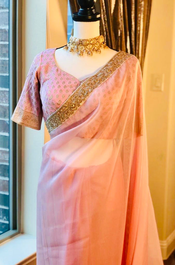 pink tissue saree adorn with golden zari borders paired with Banarasi blouse.