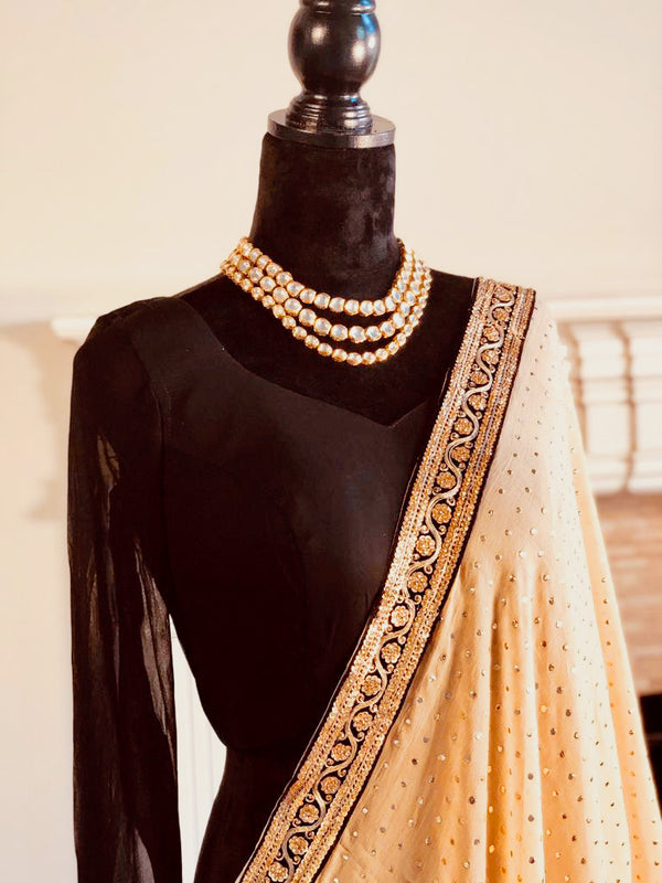 Badla work saree adorn with velvet embroidered borders paired with black chuddi sleeves blouse