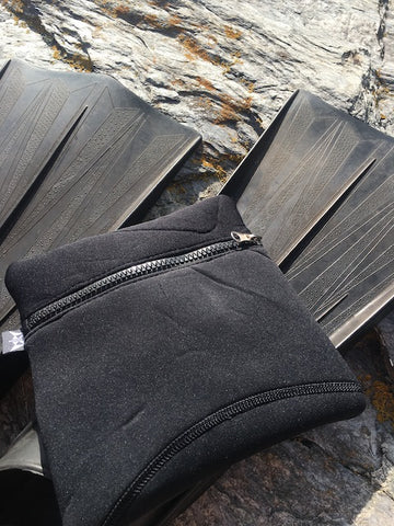 Balance square neoprene pouch in black at Piskies cove beach in Cornwall, on dive fins.