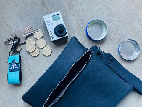 Mindful Manta neoprene pouch in black surrounded by adventure camera, keyring, loose change and lip balm.