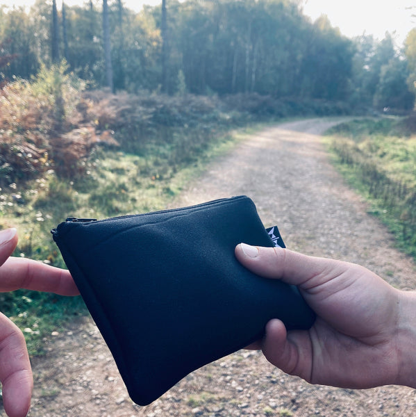 Earthbound Rectangle Neoprene Pouch in Black on a woodland walk
