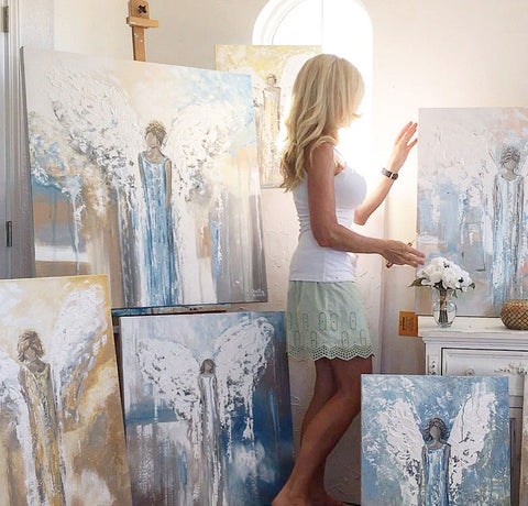 Contemporary Artist Christine Krainock in studio with abstract angel painting collection