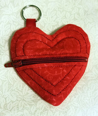 Red, quilted, heart shaped coin purse is about 3 inches at its widest point. There is a red zipper horizontally through the middle and a tab with a key ring at the top.