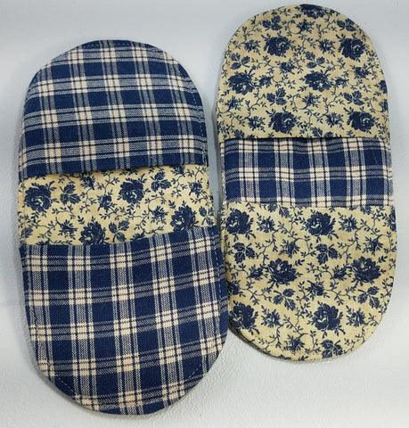 two oval shaped potholders in dark blue and tan. Each has two pockets for fingers, one at each end of the oval. One has blue floral on tan in the background and the pockets are a coordinating blue and tan plaid. The other has the plaid fabric in the background and the floral fabric for the pockets