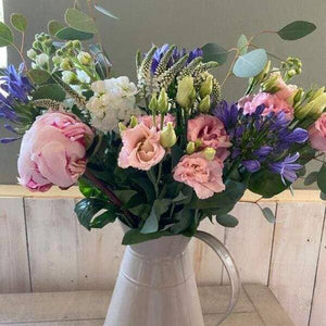 lovely mixed flowers bouquet arranged in a jug