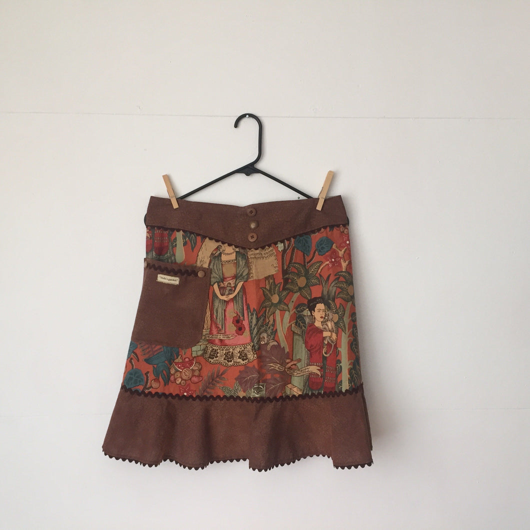 A classic Frida Kahlo motif on a cinnamon colored background. Aprons are one size with two 30 inch ties that comfortably fit most body types. 100% cotton fabric, machine wash and dry.