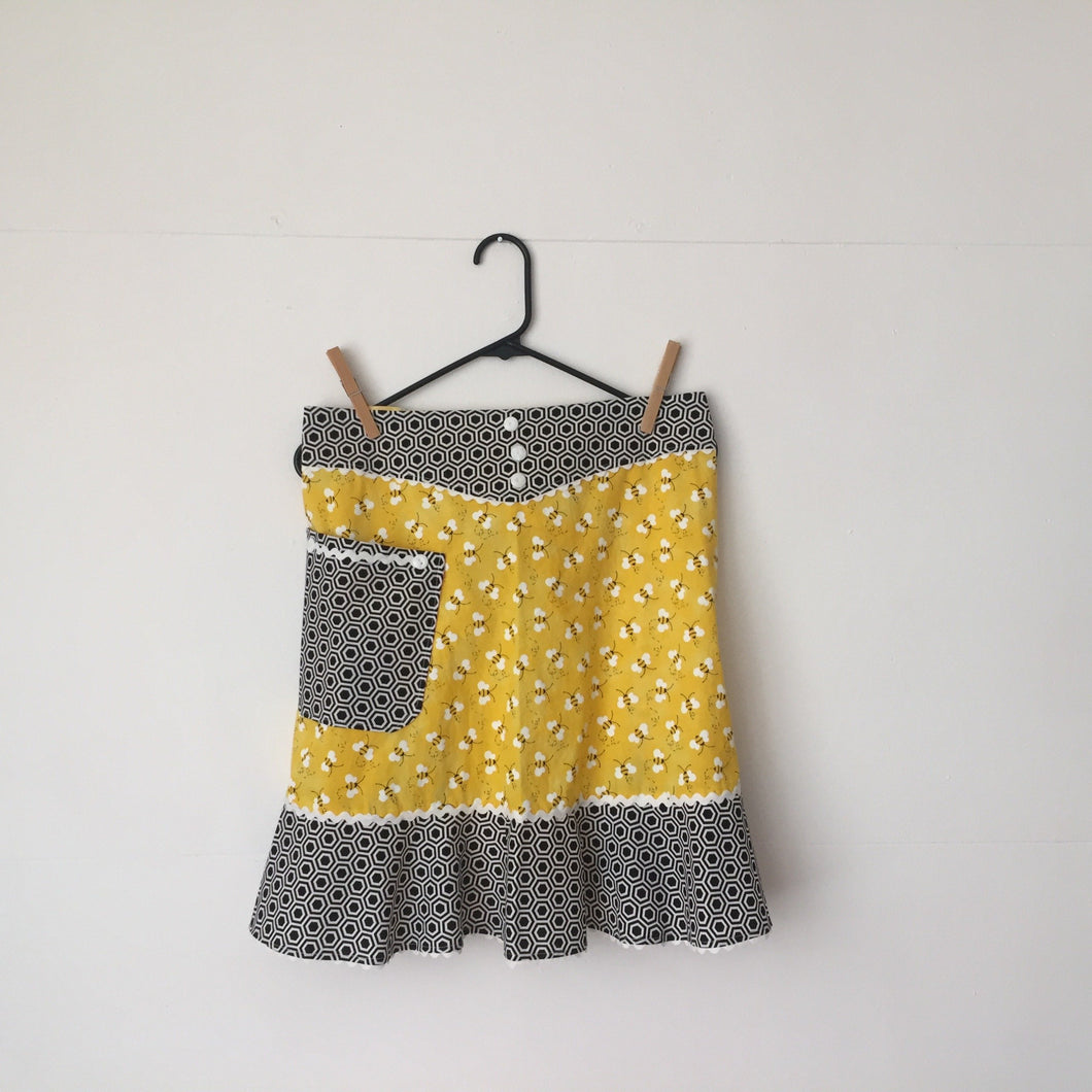 Bees tossed on a bright yellow background with black and white hexagon ruffle. Aprons are one size with two 30 inch ties that comfortably fit most body types. 100% cotton fabric, machine wash and dry.