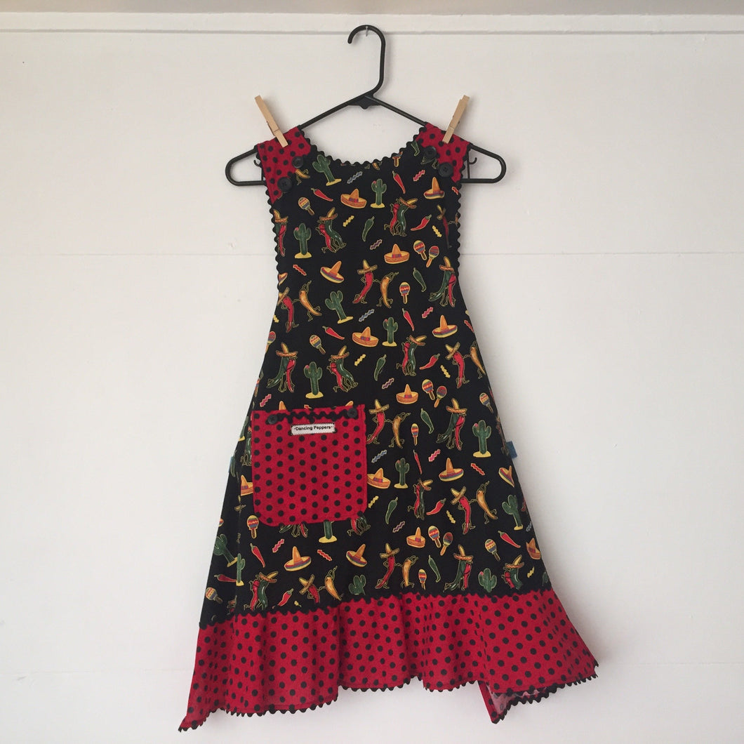 Red and green chiles dancing on black background. Aprons are one size with two 30 inch ties that comfortably fit most body types. 100% cotton fabric, machine wash and dry.