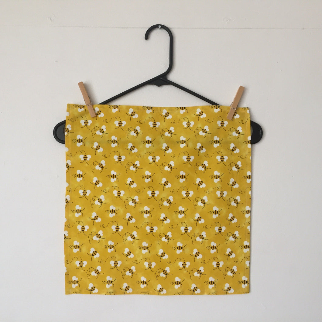 Set of four napkins with bees tossed on a bright yellow background. 100% cotton fabric, machine wash and dry.