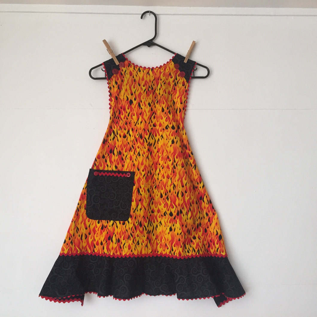 Small bright red, yellow, and orange flames on a black background. Aprons are one size with two 30 inch ties that comfortably fit most body types. 100% cotton fabric, machine wash and dry.
