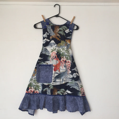 An Asian theme with koi and botanicals in a dark blue with a white dot ruffle.  Aprons are one size with two 30 inch ties that comfortably fit most body types. 100% cotton fabric, machine wash and dry.