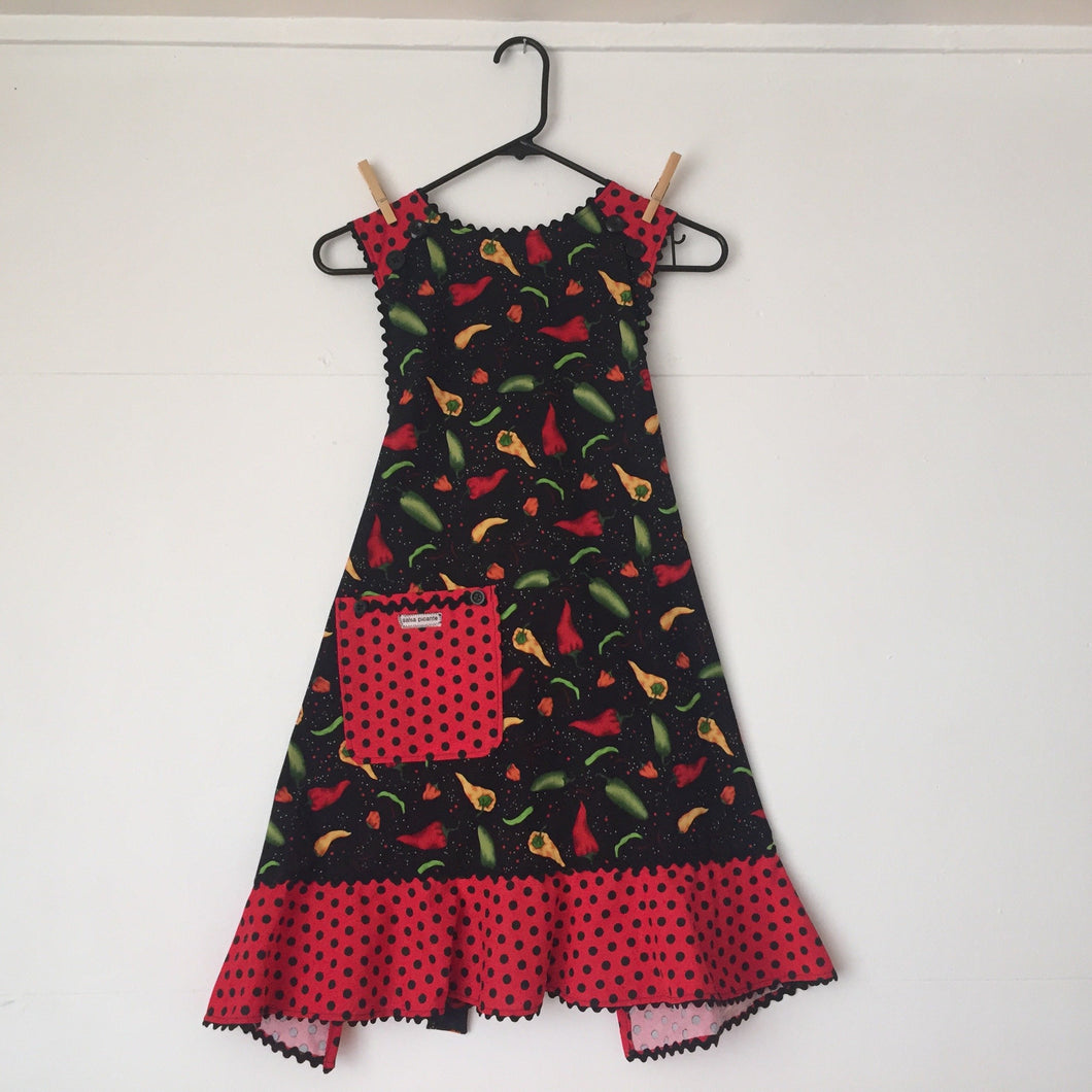 Red, green, yellow chile peppers on a black background.  Aprons are one size with two 30 inch ties that comfortably fit most body types. 100% cotton fabric, machine wash and dry.