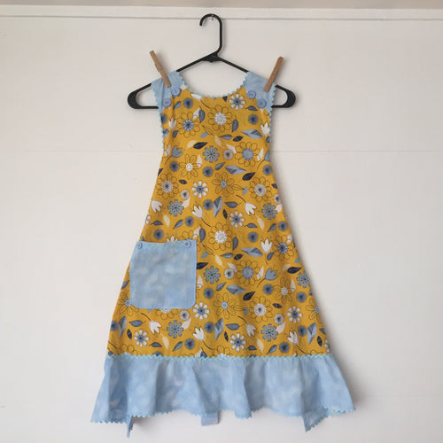 Light hearted flowers in pale blue on golden background. Aprons are one size with two 30 inch ties that comfortably fit most body types. 100% cotton fabric, machine wash and dry.