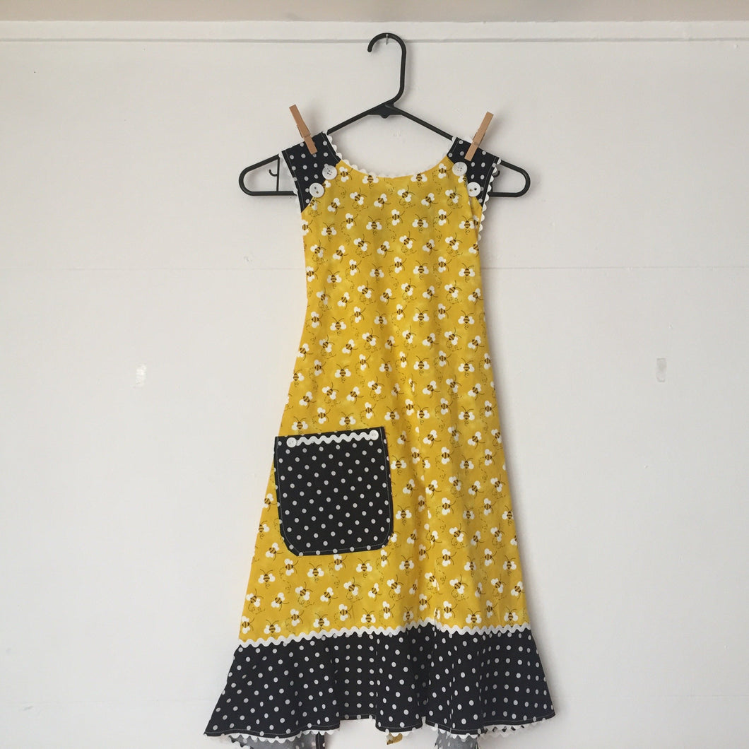 Bees tossed on bright yellow with black and white curlique motif ruffle. Aprons are one size with two 30 inch ties that comfortably fit most body types. 100% cotton fabric, machine wash and dry.