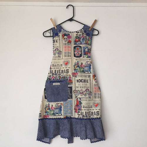 Image of apron with fabric printed with  Day of the Dead and Frida Kahlo motifs.