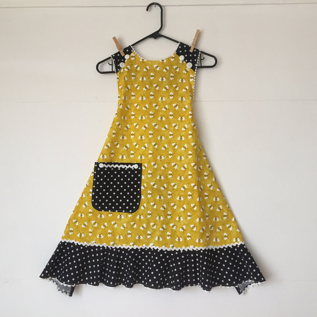 Bees tossed on bright yellow with a white large polka dot ruffle. Aprons are one size with two 30 inch ties that comfortably fit most body types. 100% cotton fabric, machine wash and dry.
