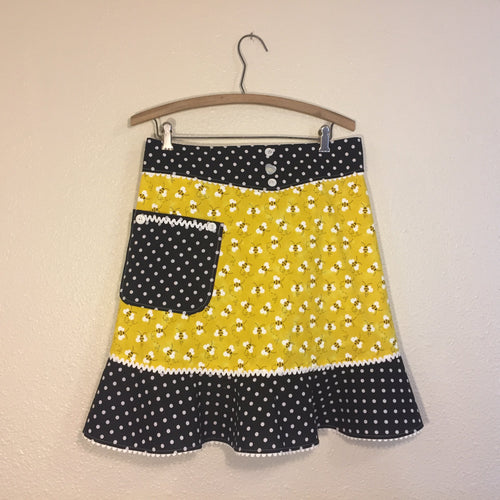 Bees tossed on a bright yellow background with black and white polka dot ruffle. Aprons are one size with two 30 inch ties that comfortably fit most body types. 100% cotton fabric, machine wash and dry.