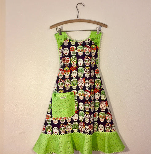 Image of apron with fabric printed with artist Frida Kahlo and sugar skulls