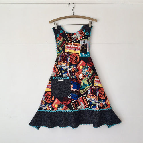 Indulge in your love of travel with this frightfully fun apron featuring vintage travel posters for all your favorite haunts and ghouls! Turquoise rickrack pops on this black background with a curlique black and grey ruffle. Aprons are one size with two 30 inch ties that comfortably fit most body types. 100% cotton fabric, machine wash and dry.