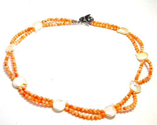 Vintage coral beads in shades of orange complimented by fresh water coin pearls in a 17 inch necklace.