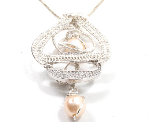 A shape woven pendant with two fresh water pearls and a pave crystal band. it is 2.5 inches long on an 18 inch chain