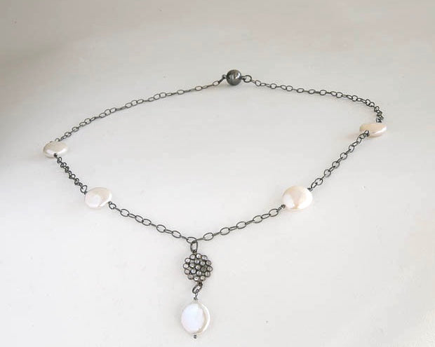 Fresh water coin pearls with sapphire floral accent on an oxidized sterling silver chain. It is 20 inches long.