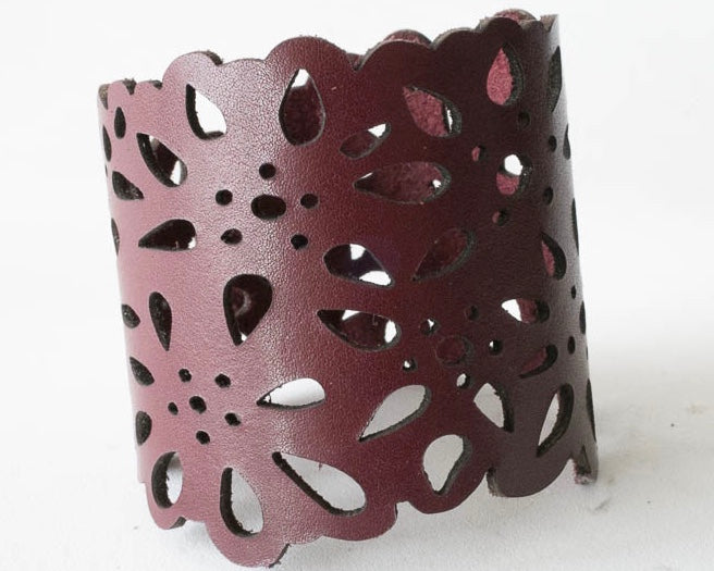 Two inch wide leather cuff laser cut with a flower design.