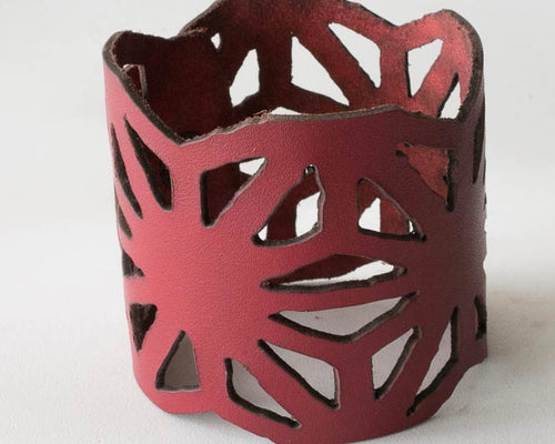 Square cut laser cut leather cuff with snap closure.