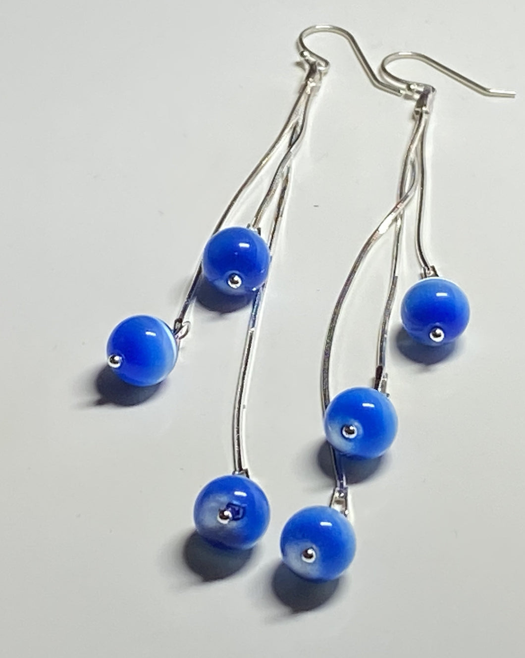 Long blue and silver earrings, 3 inches long, three round beads dangling from silver.