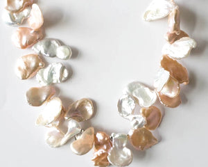 Fresh water keshi pearl necklace in peaches and cream. It is 16 inches long with a sterling silver box clasp.