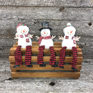 Sitting snowman with plaid dangling legs