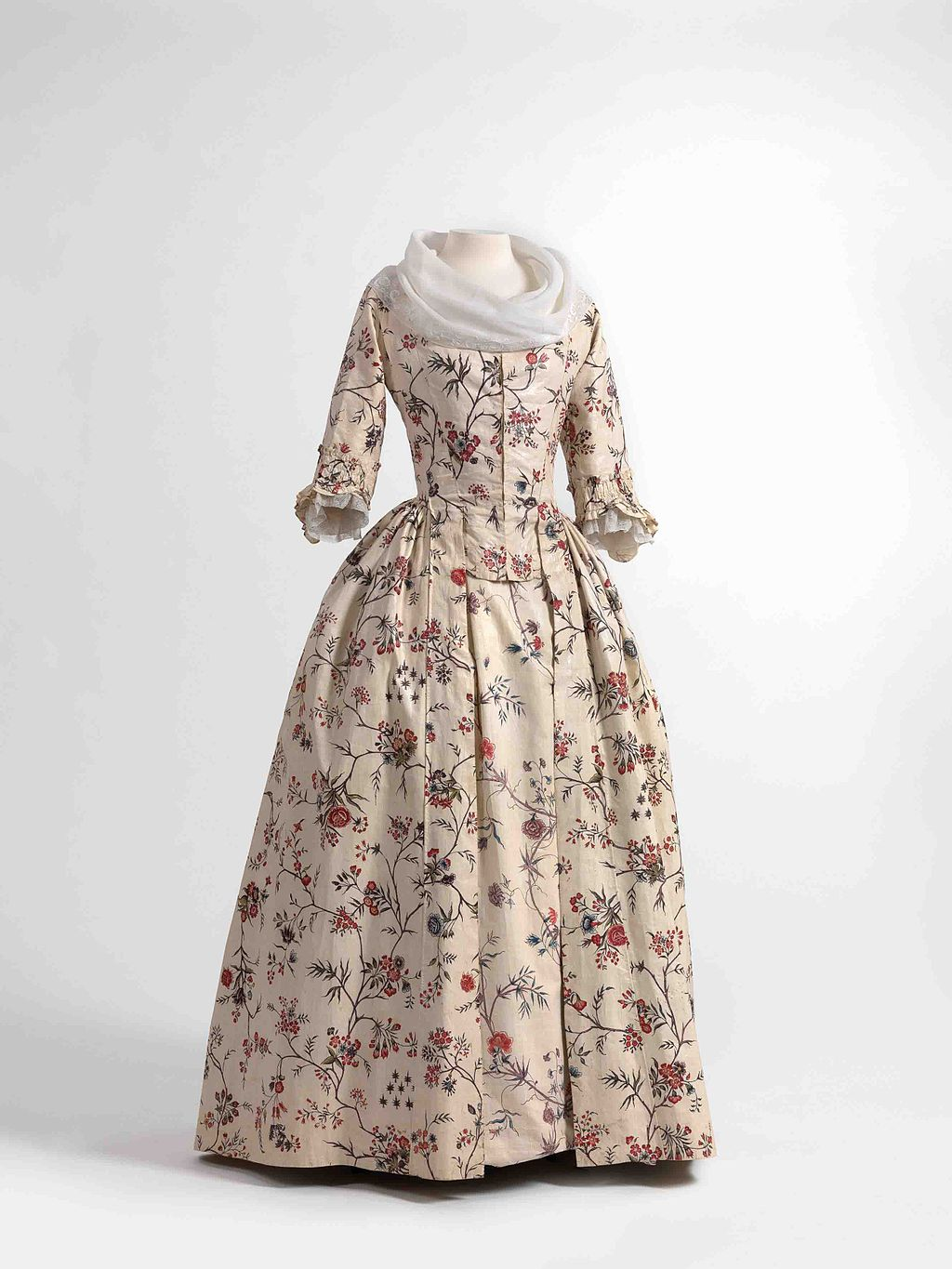 Dress (robe à l'anglaise) and skirts in chintz, ca. 1770-1790, shawl (fichu) in embroidered batiste, 1770-1800. Jacoba de Jonge Collection in MoMu - Fashion Museum Province of Antwerp, www.momu.be / Photo by Hugo Maertens, Bruges, CC BY-SA 3.0 <https://creativecommons.org/licenses/by-sa/3.0>, via Wikimedia Commons