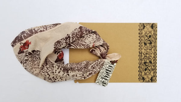 Naturally dyed organic cotton bandana, heritage chicken print tied with tag and printed minimal packaging example